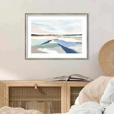 Tan wall with abstract landscape painting above light brown desk.