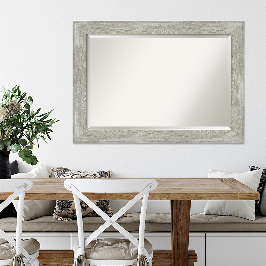 Grey colored wood framed mirror above sitting area.