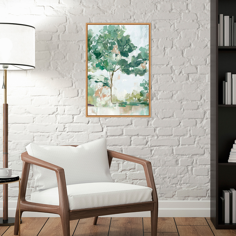 Abstract tree painting next to short chair and lamp