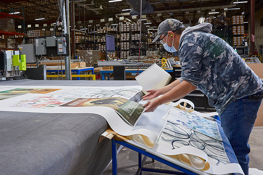 Worker collecting pieces of art off assembly line.