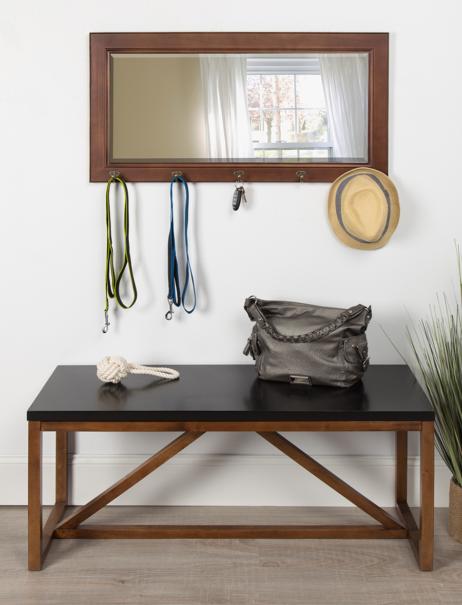 Mirror with hooks adorned with goods above a bench