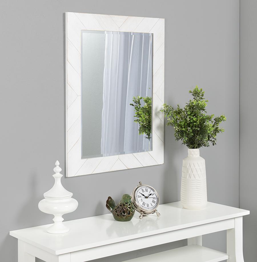 White framed mirror above white desk.