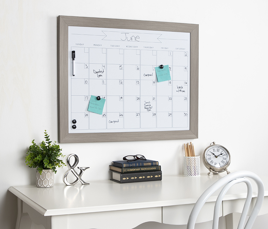 Erasable calendar board above a white desk featuring a clock, plant, books, and silver ampersand sculpture.