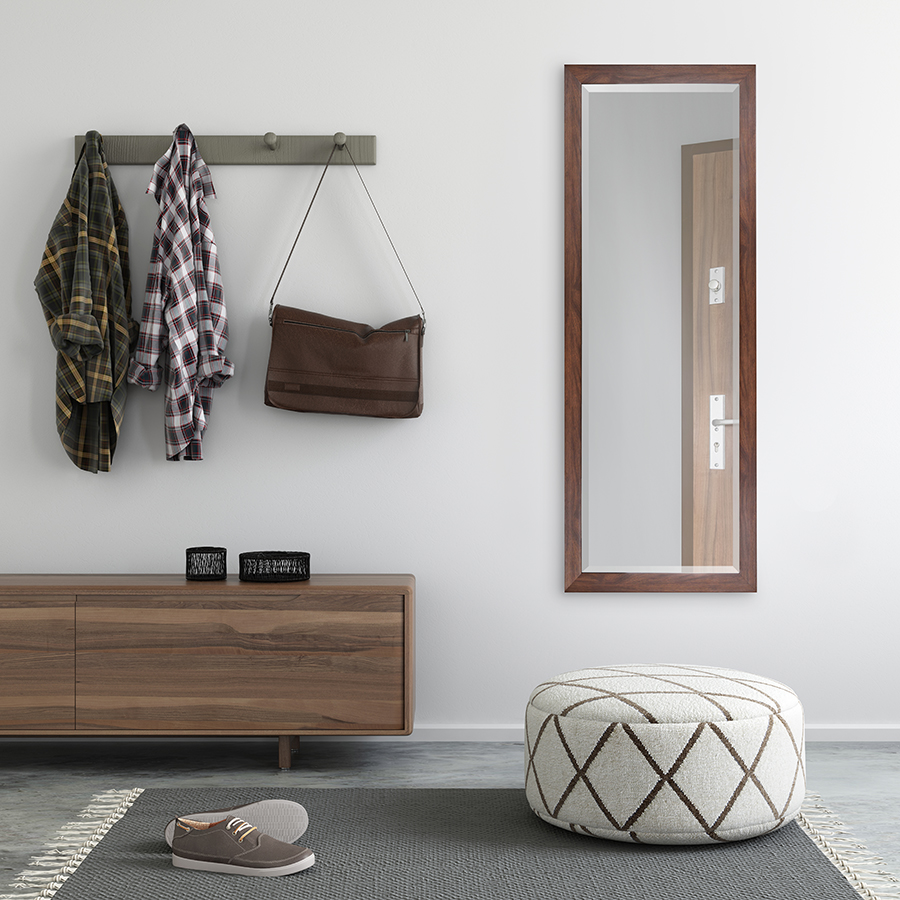 Home entryway with mirror, coatrack, and large wood framed mirror
